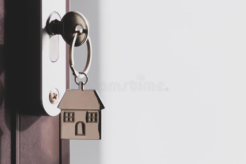 The home key with house keyring in the door keyhole with copy space royalty free stock photography