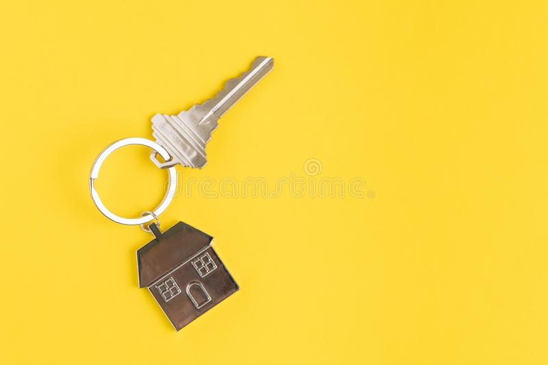 Home key with house keyring or keychain on solid yellow background using as home ownership, mortgage or buy and sell property and. Real estate stock photo