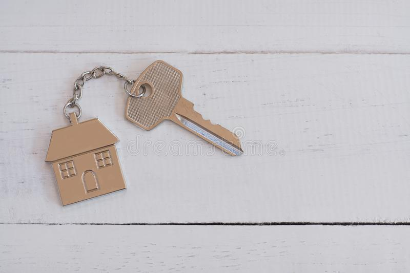 Home key with house keyring on white wood table background, property concept. Copy space stock photos