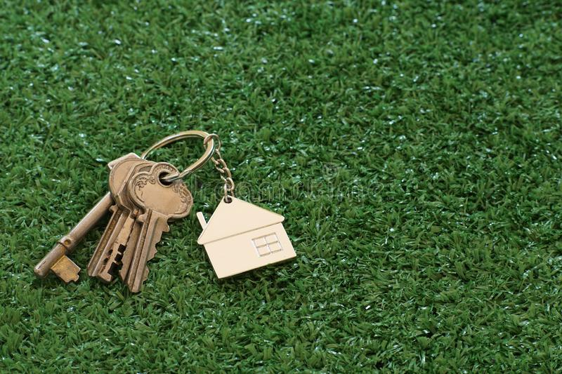 Home key with house keyring on white wood table background, property concept. Copy space royalty free stock image