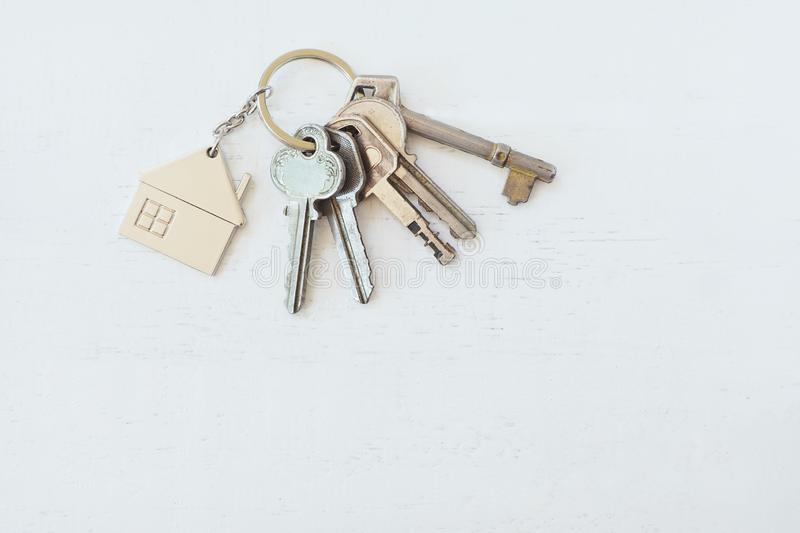 Home key with house keyring on white wood table background, property concept. Copy space royalty free stock photo