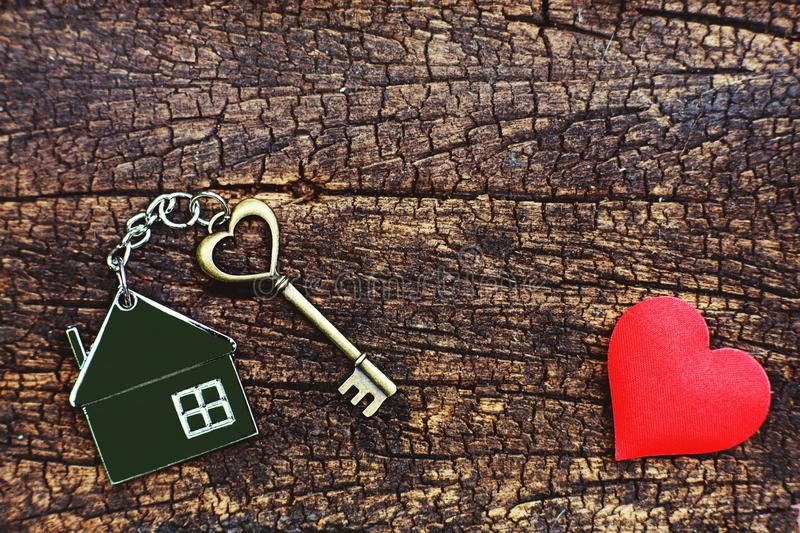 Home key with love house keyring decorate with mini heart on wood background, sweet home concept royalty free stock images