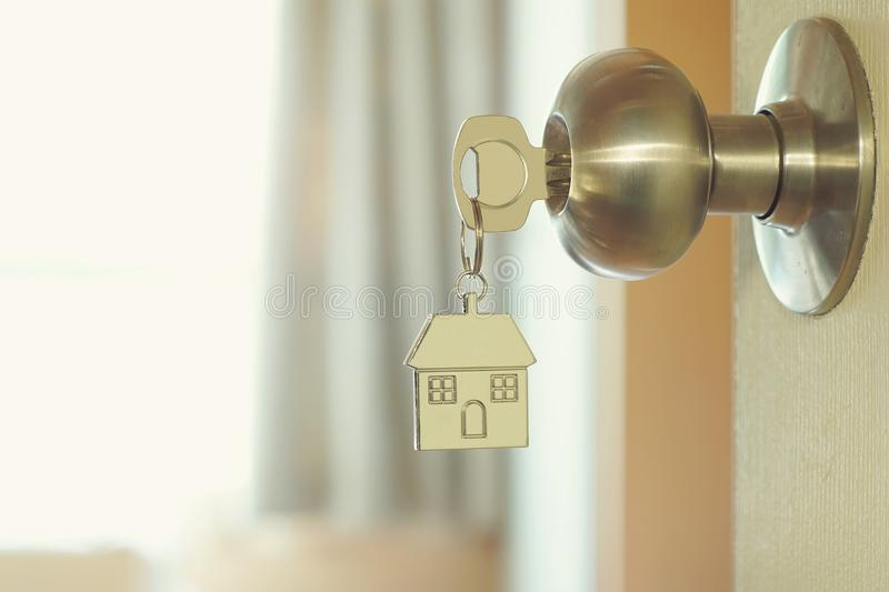 Home key with house keychain in keyhole, property concept stock photo