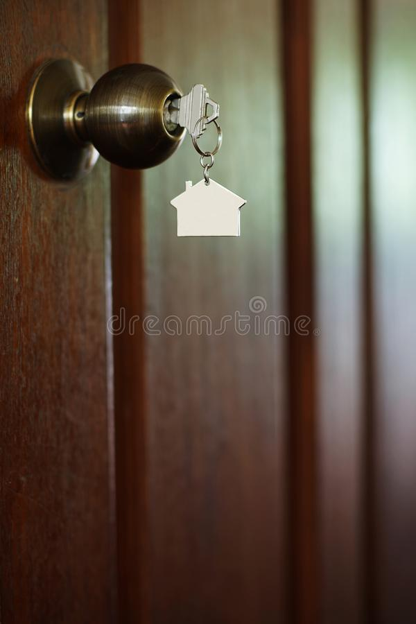 Home key with house keychain in keyhole, property concept. Home key with metal house keychain in keyhole, property concept royalty free stock photo