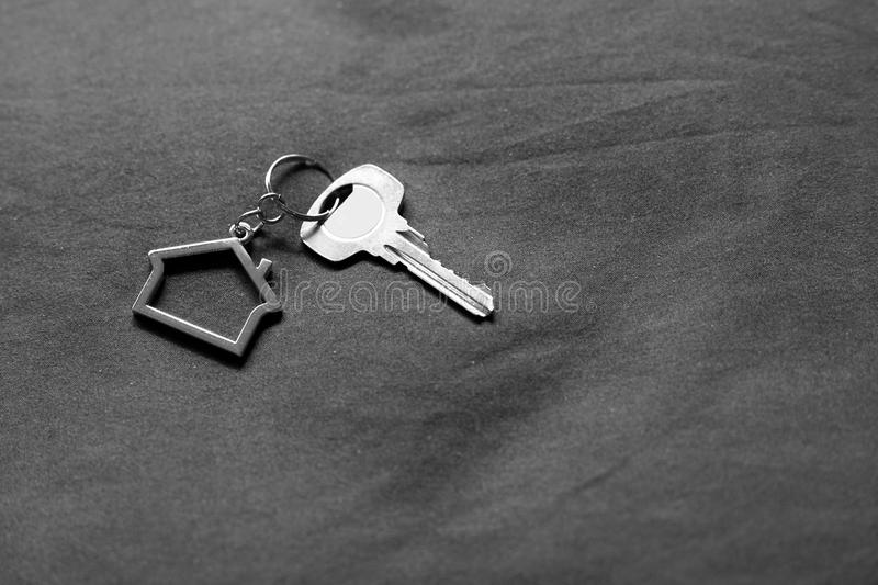 Home key with house keyring on bed in black and white, property concept, copy space. Home key with metal house keyring on bed in black and white, property stock image