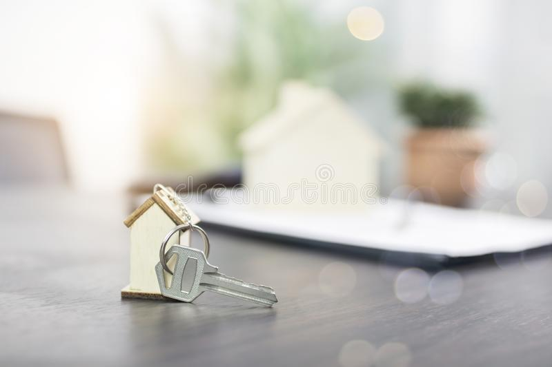 Home key on table of bank agency. Resident model and paper contract ready for customer, house and estate concept stock image