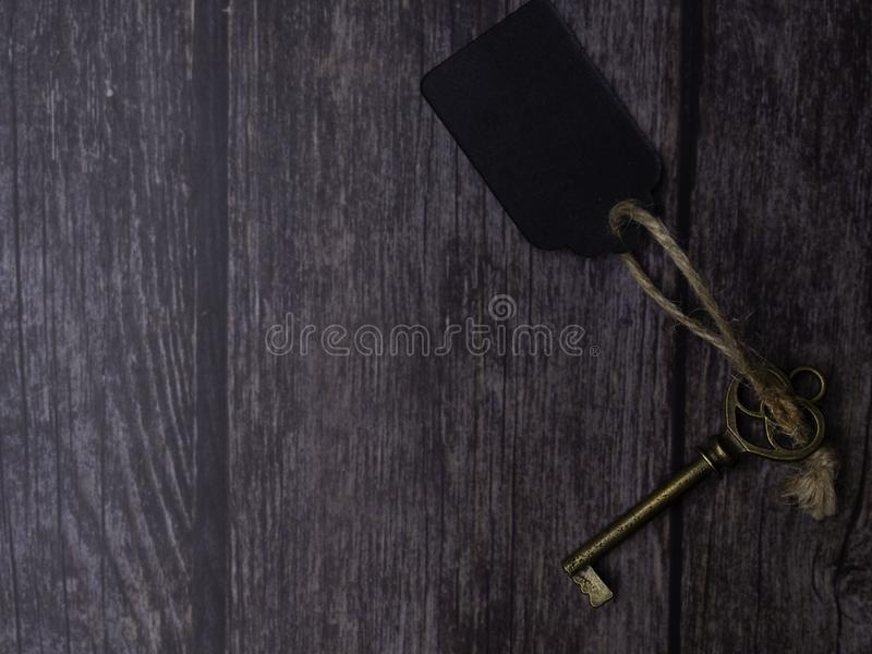 Home key with tag on wood table background, property concept, copy space. Top view royalty free stock images