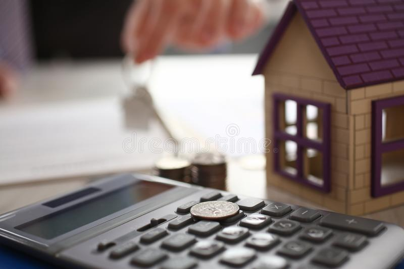 Home Keychain in Real Estate Agent Hand House Rent. Property Loan Sale Concept. House, Calculator. Bank Credit for Residential Purchase. Appertment Sell Items royalty free stock photo