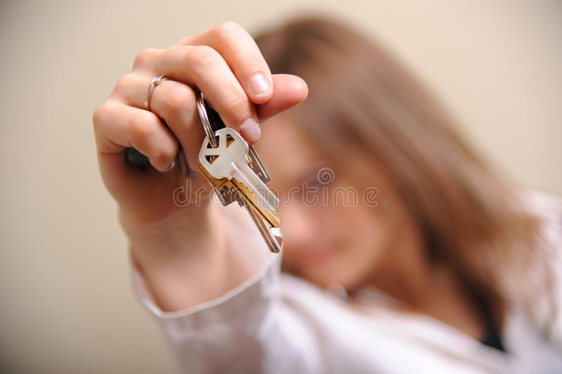 Home keys. Young lady holding home keys royalty free stock photo