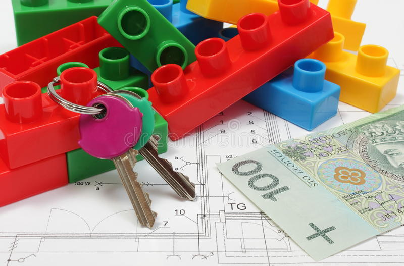 Home keys, colorful building blocks and money on housing plan. Closeup of home keys, heap of colorful building blocks and banknote lying on construction drawing stock image