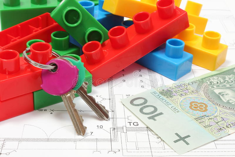 Home keys, colorful building blocks and money on housing plan. Closeup of home keys, heap of colorful building blocks and banknote lying on construction drawing stock photography