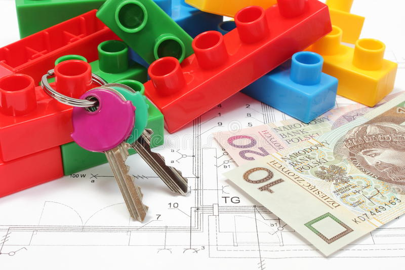 Home keys, colorful building blocks and money on housing plan. Closeup of home keys, heap of colorful building blocks and banknote lying on construction drawing royalty free stock photo