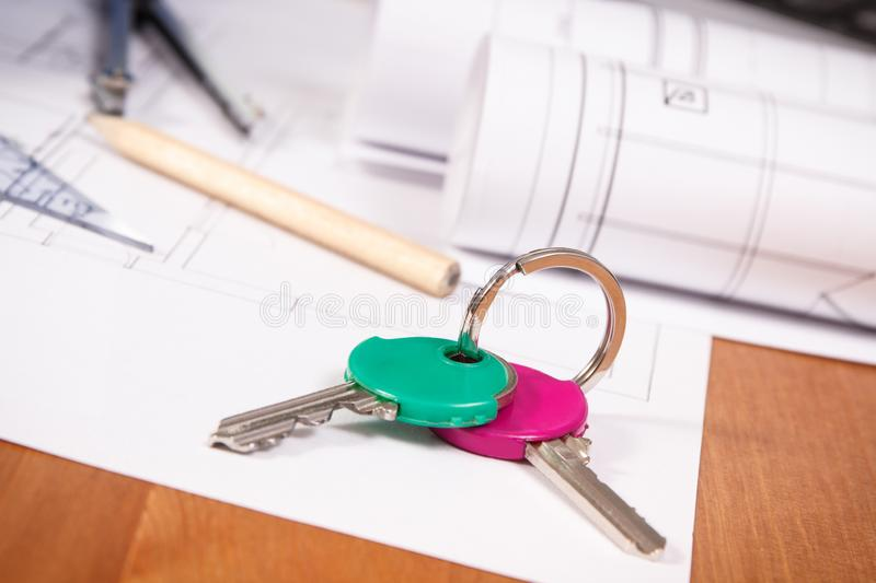 Home keys and electrical diagrams or blueprints with accessories for engineer jobs, building home concept. Home keys, electrical diagrams or drawings and stock photography