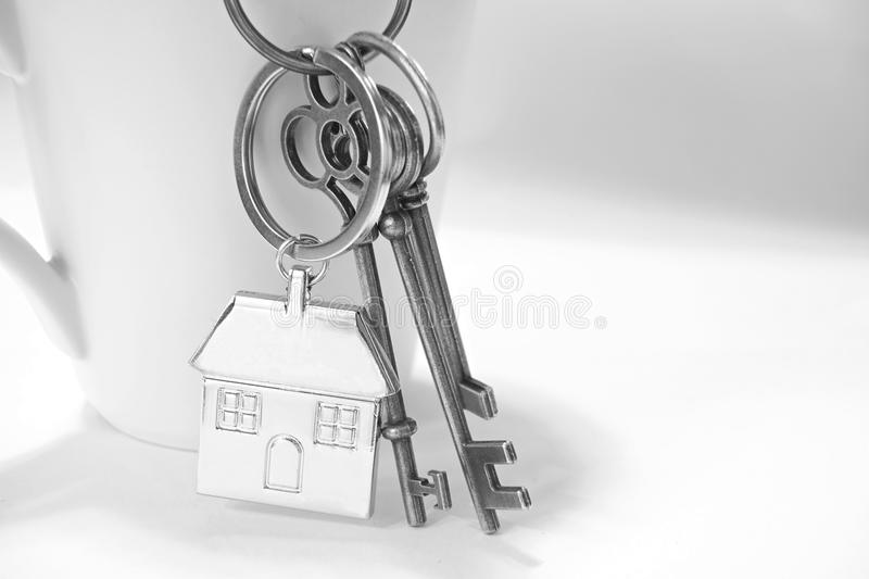 Home keys with house keyring hanging on white coffee cup. High key tone, black and white, b&w stock photos