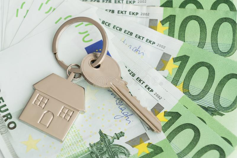 Home keys and a small house on currencies euro background royalty free stock image