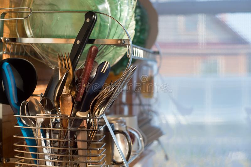 Home kitchen. Clean washed dish ware drying on a drainer mounted in kitchen. Clean dishes: spoon, plate, cup, knife, fork after. Washing on the shelf royalty free stock images