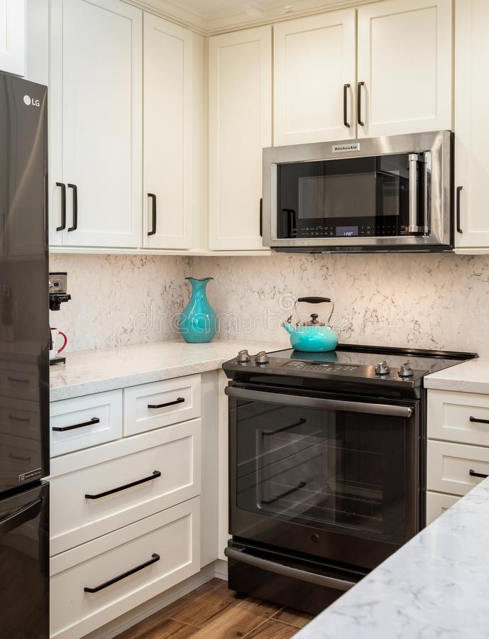 Home kitchen design remodel with white cabinets. Home small kitchen design remodel with white cabinets, stainless appliances stock photos