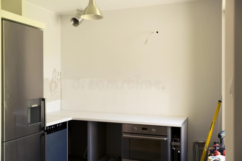 Home and kitchen renovation. Unfinished kitchen remodeling. Construction site with construction tools stock image