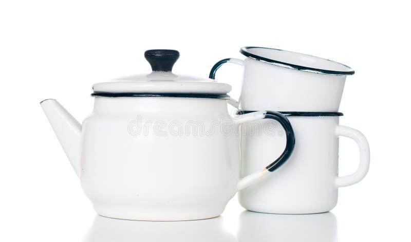 Home kitchenware. Vintage enameled kettle and mugs isolated on white background royalty free stock photos