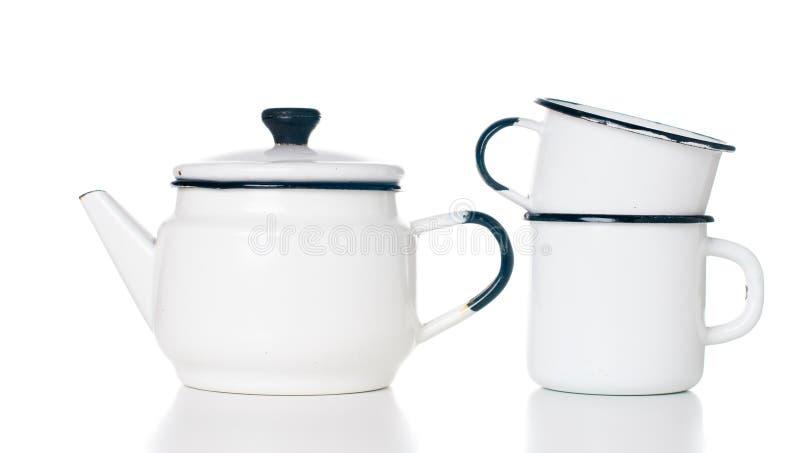 Home kitchenware. Vintage enameled kettle and mugs isolated on white background stock photos