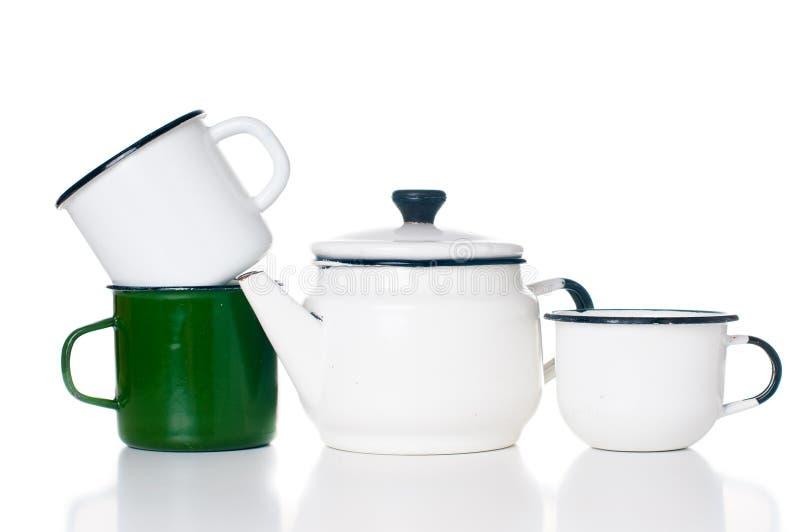 Home kitchenware. Vintage enameled kettle and mugs isolated on white background royalty free stock photography