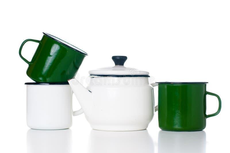 Home kitchenware. Vintage enameled kettle and mugs isolated on white background royalty free stock image