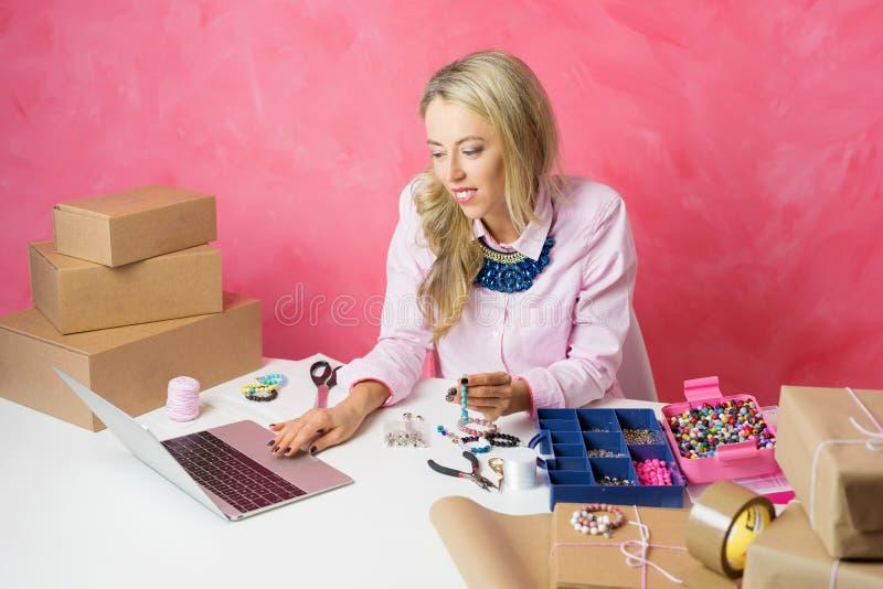 home kvinnaworking Göra smycken och försäljningar dem direktanslutet royaltyfri bild