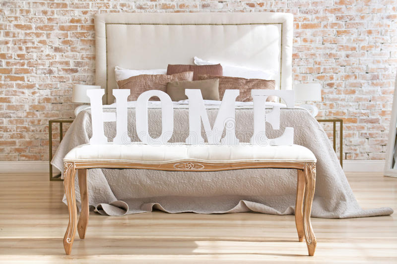 Home letters sign in interior near bed closeup stock photos