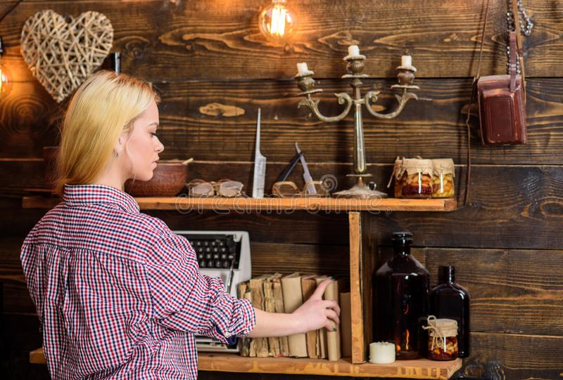 Home library concept. Girl looking for book in house of gamekeeper. Girl in casual outfit in wooden vintage interior royalty free stock photography