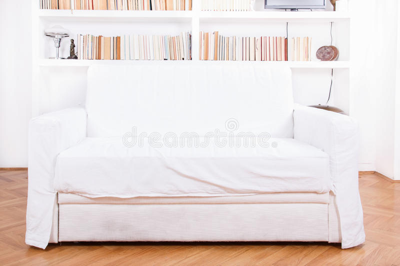 Home library with sofa or couch. Clean and modern decoration. White living room with modern wooden white bookshelf and different books inside, domestic royalty free stock images