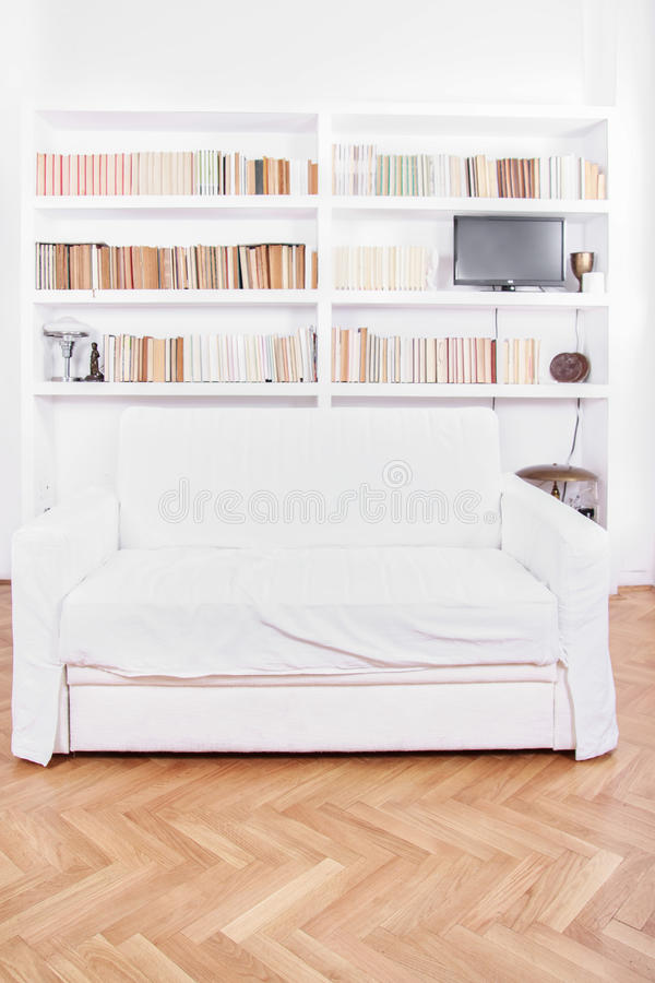Home library with sofa or couch in white living room. Home library with sofa or couch. Clean and modern decoration, white living room with modern wooden white royalty free stock photo