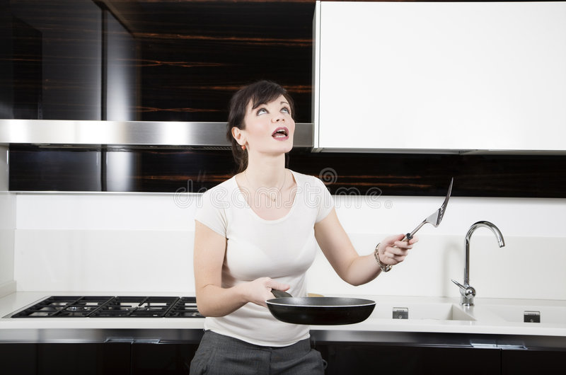 Home life. Woman making a mess with omelets stock photography