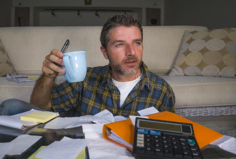 Home lifestyle accounting portrait of young attractive and relaxed man counting monthly expenses and payments doing paperwork stock photo