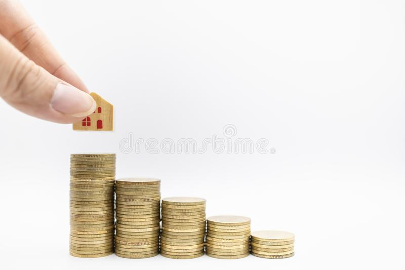 Home loan, business, money and saving concept. Close up of hand holding wooden house toy and putting down on top of stack of gold stock images