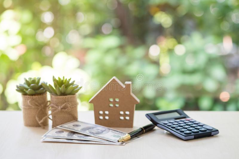 House model with pile of dollar bills, calculator, pen and plant. Home Loan, mortgage and real estate concept, House model with pile of dollar bills, calculator royalty free stock photos