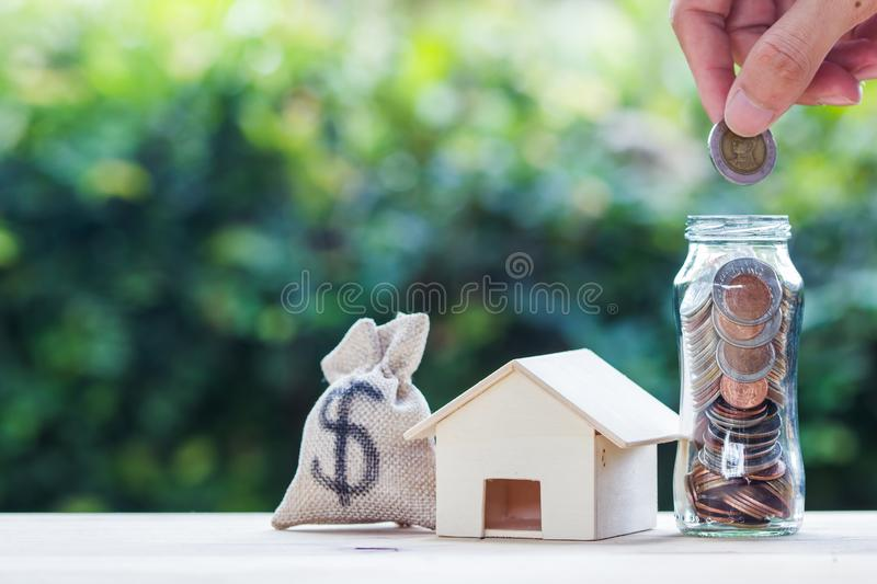 Home loan, mortgages, debt, savings money for home buying concept : Hand holding coin over glass jar. US dollar in a money bag, royalty free stock images