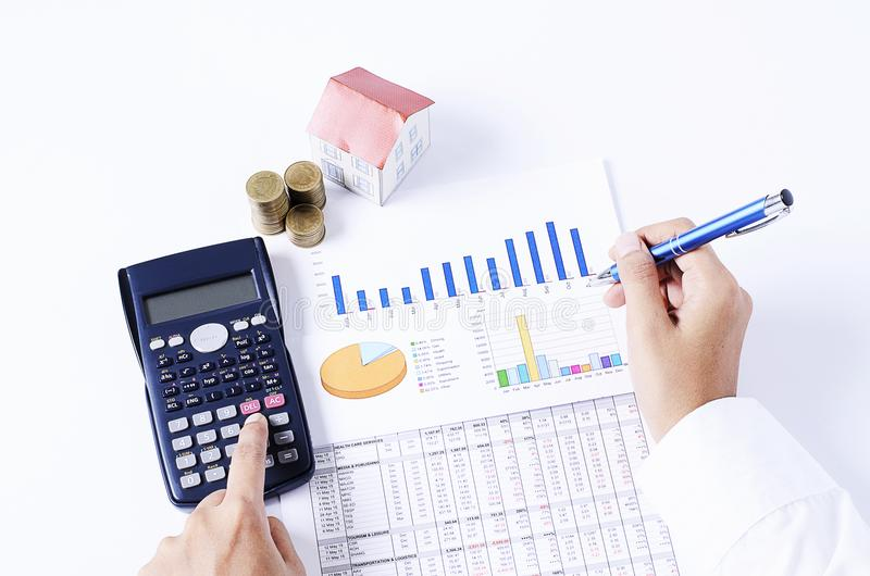 Home loans concept with hand holding calculator with business do. Cument chart stock photography
