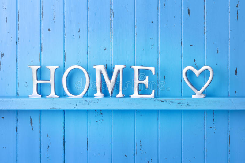 Home Love Blue Background. A rustic blue painted wood background with the word home spelled out in metal letters and a love heart symbol