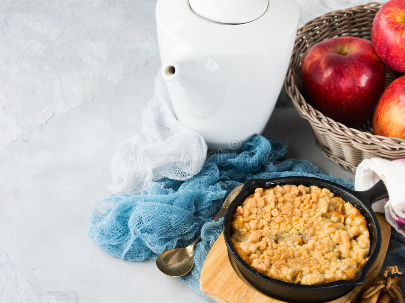 Home made apple crumble in cast iron skillet for breakfast. Home made apple crumble in cast iron skillet on wooden serving board. Cozy and healthy breakfast set royalty free stock photography