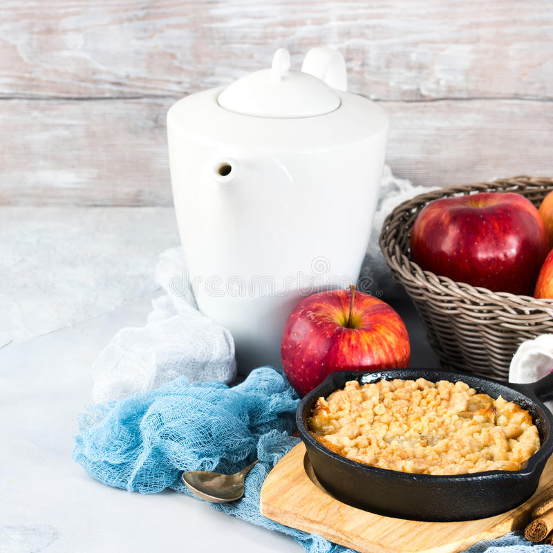 Home made apple crumble in cast iron skillet. Square. Home made apple crumble in cast iron skillet on wooden serving board. Cozy and healthy breakfast set with stock photos
