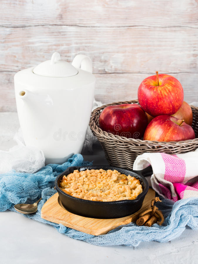 Home made apple crumble in cast iron skillet. Vertical. Home made apple crumble in cast iron skillet on wooden serving board. Cozy and healthy breakfast set with royalty free stock photography