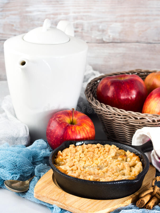 Home made apple crumble in cast iron skillet. Vertical. Home made apple crumble in cast iron skillet on wooden serving board. Cozy and healthy breakfast set with stock images