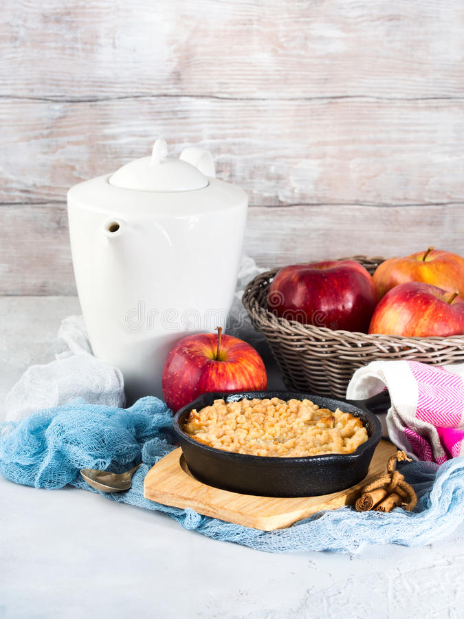 Home made apple crumble in cast iron skillet. Vertical. Home made apple crumble in cast iron skillet on wooden serving board. Cozy and healthy breakfast set with stock photo