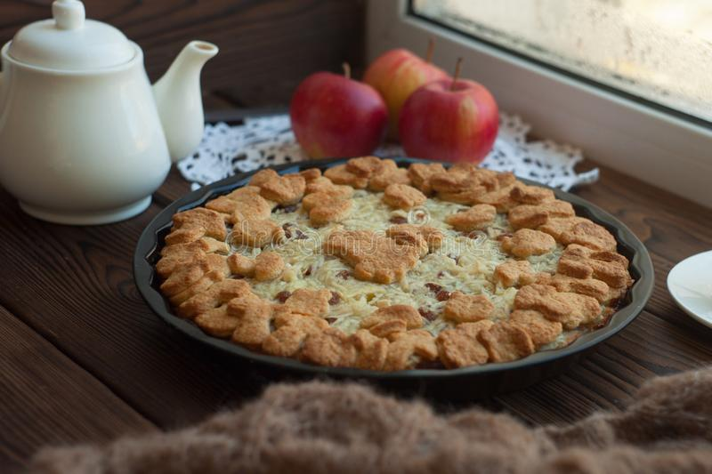 Home made apple crumble in cast iron skillet on wooden background near the window, Cozy and healthy breakfast set with fruit. Home made apple crumble in cast stock images