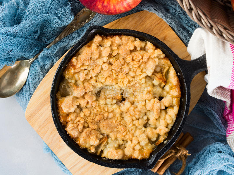 Home made apple crumble in cast iron skillet. On wooden serving board. Cozy and healthy breakfast set with fruit royalty free stock photo