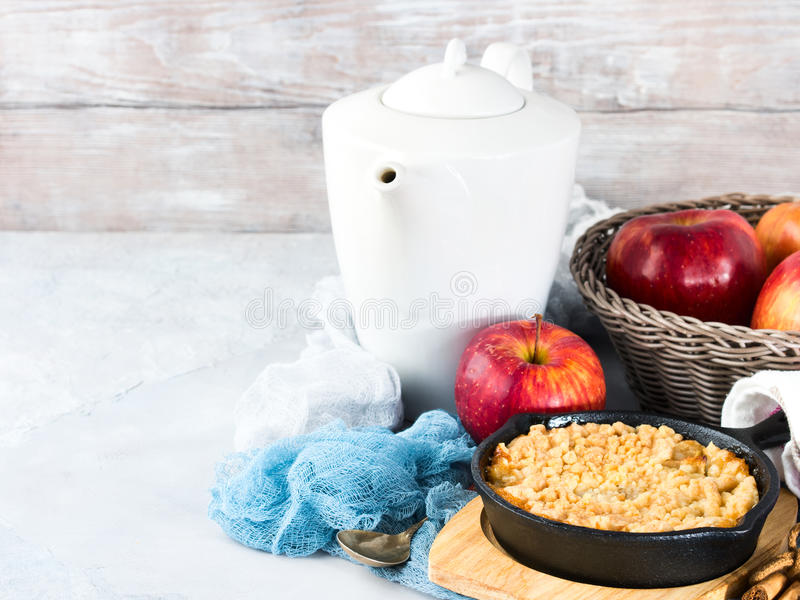 Home made apple crumble in skillet. copy space. Home made apple crumble in cast iron skillet on wooden serving board. Cozy and healthy breakfast set with fruit stock photo