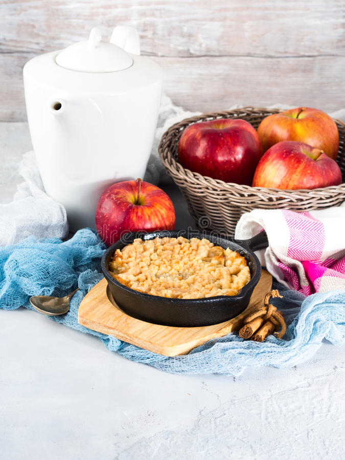 Home made apple crumble in skillet. Vertical. Home made apple crumble in cast iron skillet on wooden serving board. Cozy and healthy breakfast set with fruit stock image