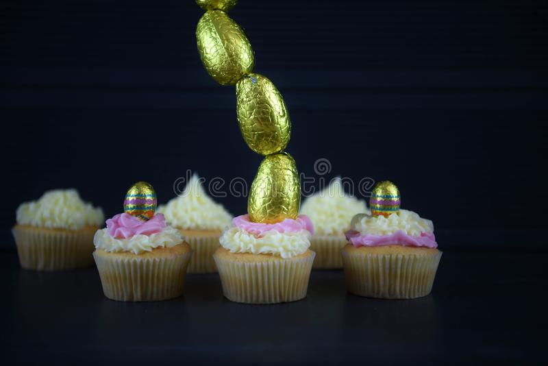 Easter cakes with golden eggs in a vertical line for creative decorations. Home made and baked vanilla sponge mini cakes or cupcakes with frosting on top stock photos