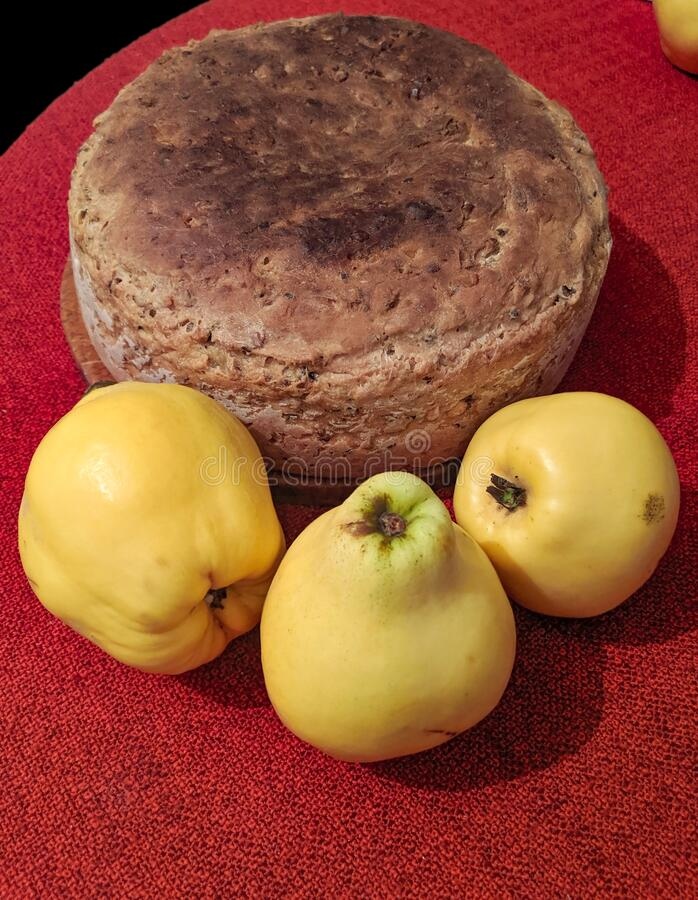 Home made bread and three Quince fruits on the red fabric royalty free stock photos