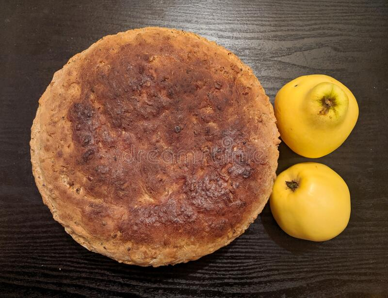 Home made bread and  two Quince fruits on wooden board royalty free stock images